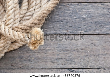 Big navy rope on wooden plank focusing on the end of the rope, can be use as background of powerpoint - stock photo