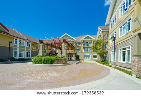 Big nicely paved plaza, yard with decorative entrance, surrounded with new townhouses. Living complex. - stock photo