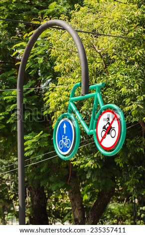 Big notice for bicycle lane hanging on black pole in green park - stock photo