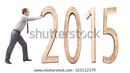 Big obstacle concept in 2015, businessman move a boulder with a text of 2015 Young business man try to compose date in studio, isolated over white background - stock photo