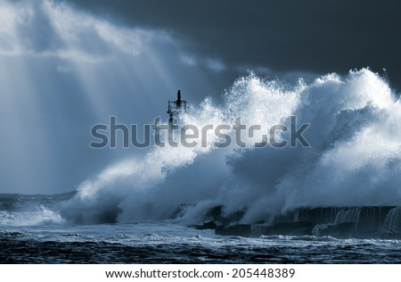 Big ocean wave over lighthouse against dramatic enhanced sky with sunbeams. Toned blue. North of Portugal. - stock photo