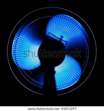big office fan in blue light isolated on black - stock photo