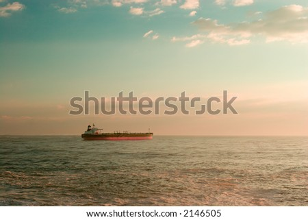 Big oil ship leaving the harbour, early morning - stock photo