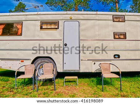 Big Old American RV / Camping Car with Chairs in Pine Forest Setting - stock photo