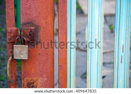 Big old antique iron lock hangs on a rusty closes the entrance door - stock photo