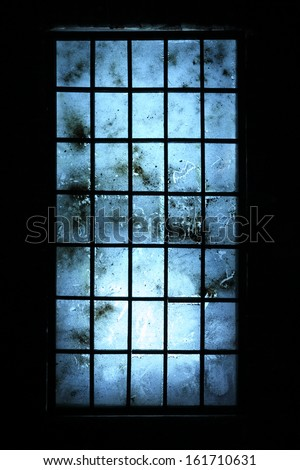Big old dirty window with blue scratched glasses in dark room.