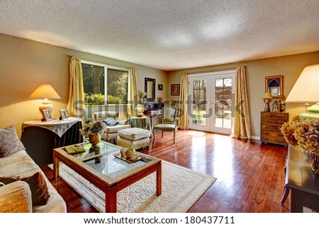 Big old living room with hardwood floor, couch, coffee table and antique chest, chairs.