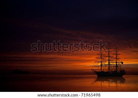big old sailboat on beautiful sunset - stock photo
