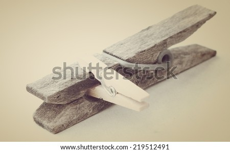 Big old wooden rusty clothespin and a small tweezer isolated on a yellowish warm vintage filter effect. - stock photo
