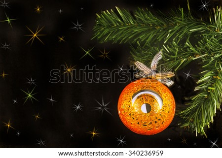Big orange shiny mirror ball on new year tree on a black background with colorful stars. - stock photo