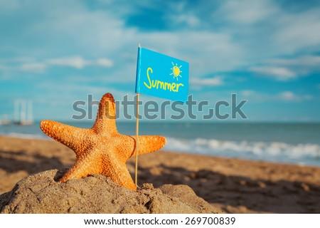 big orange starfish with flag at the seashore. Summer concept. - stock photo