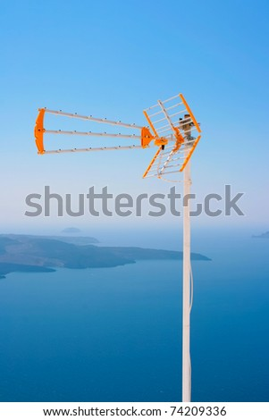 Big orange with white TV antenna against Aegean sea and part of volcano on island of Santorini in Fira, Greece. - stock photo