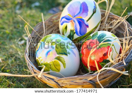 Big ostrich painted eggs in a wicker basket surrounded by grass . Easter celebration - stock photo