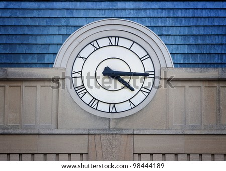 Big outside clock with Roman Numerals on stone building with blue roof - stock photo