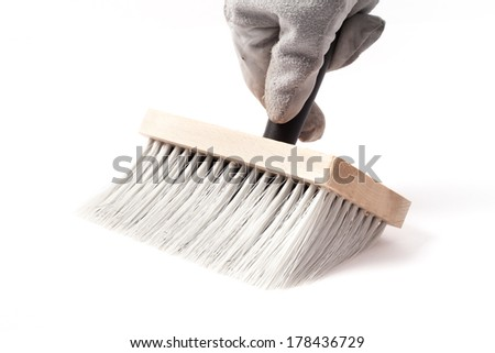 Big paintbrush in hand isolated on white background. - stock photo