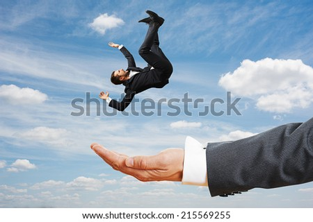 big palm catching small frightened businessman over blue sky - stock photo