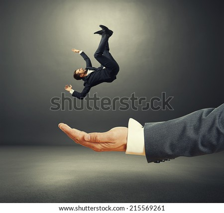 big palm catching small startled businessman in dark room - stock photo
