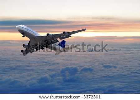 Big passenger airplane flying above the clouds and sunset - stock photo