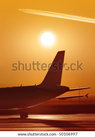 big passenger airplane is waiting for departure in airport, sunset