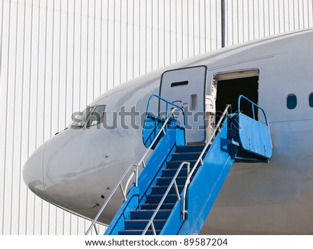 Big passenger airplane parked near hangar - stock photo