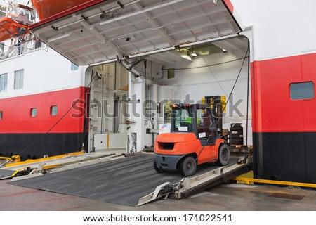 Big passenger ship loading with lift truck - stock photo