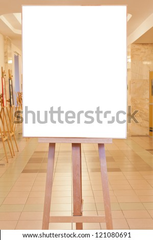 big picture frame with white cut out canvas on easel in art gallery - stock photo