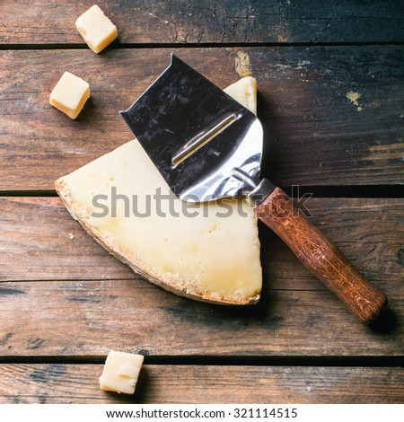 Big piece and little cubes of Belgian cheese with cheese knife over wooden background. Top view. Square image - stock photo