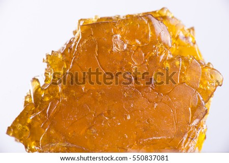 Big piece of cannabis oil concentrate aka shatter isolated over white background