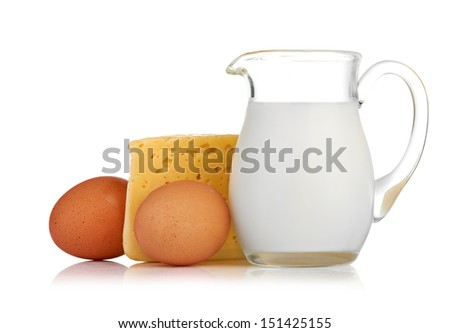 Big piece of cheese, glass jug with milk and eggs on white background