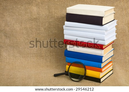 Big pile of books and magnifier glass on canvas - stock photo