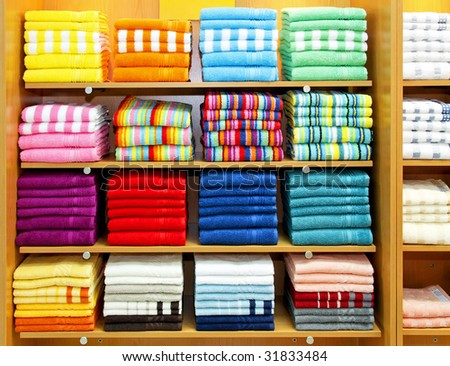 Big pile of colorful towels at shelf - stock photo