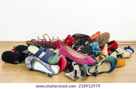 Big pile of colorful woman shoes. Untidy stack of shoes thrown on the ground. - stock photo