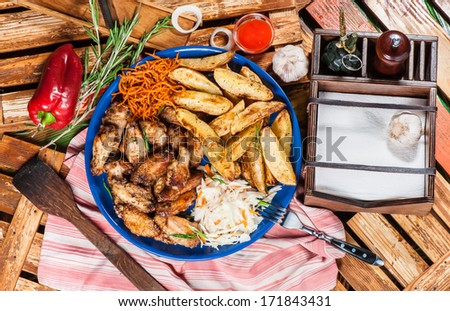 Big plate with fried chicken wings, potato and marinated carrot and cabbage - stock photo