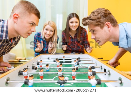 Big play. Two young boys standing bend over a hockey table looking challenging at each other trying to win a match while their girlfriends cheering them up - stock photo