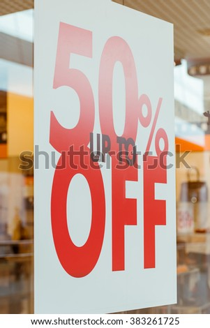Big poster showing discount and sale, hanging in shopping mall - stock photo
