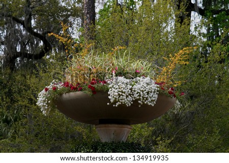 Big pot of colorful spring flowers against a lush green background. - stock photo