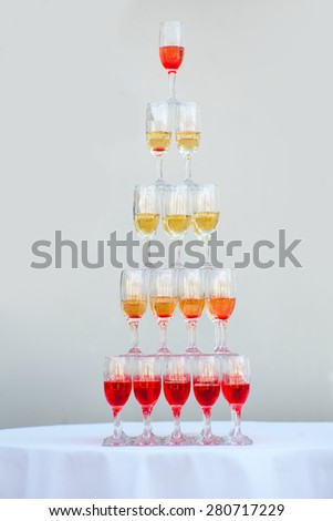 Big pyramid of wineglasses with wine or champagne white and red beverages on holiday background, vertical picture - stock photo