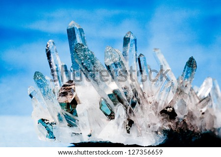 Big quartz crystals (rock crystal) with iron pyrite (fool's gold) crystals grown on. - stock photo