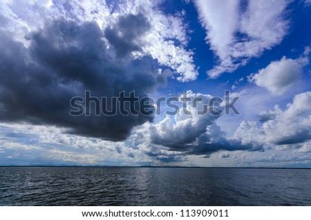 Big rain cloud coming on ocean - stock photo