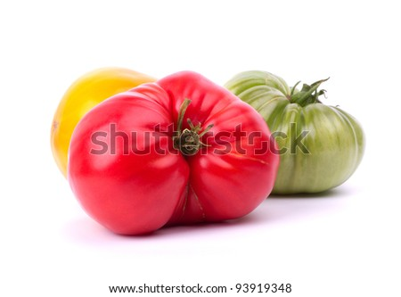 Big red, green and yellow tomatoes on white background - stock photo