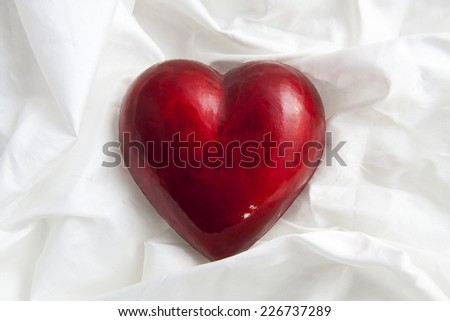 Big red heart on satin for background use - stock photo