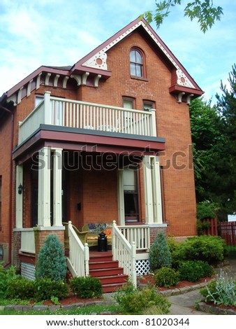 Big red house and its stairs and beautiful garden in Gananoque, Ontario, Canada, along the street by cloudy weather. - stock photo