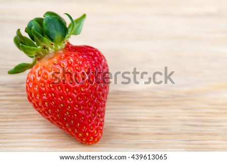 Big red ripe strawberry on wooden table, closeup, copyspace - stock photo