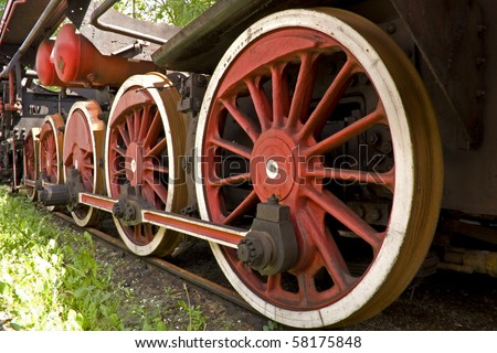 big red rusty wheels of old steam engine