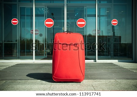 big red suitcase standing in front of the closed doors - stock photo