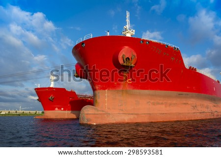 Big red tankers moored at the jetty. - stock photo