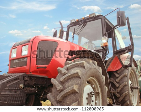 Big red tractor against the sky with clouds - stock photo