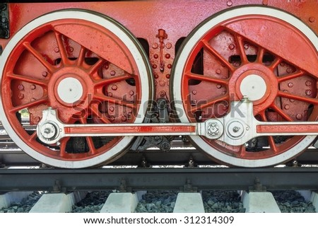 big red wheels a closeup of the vintage locomotive with the steam engine on railway tracks - stock photo