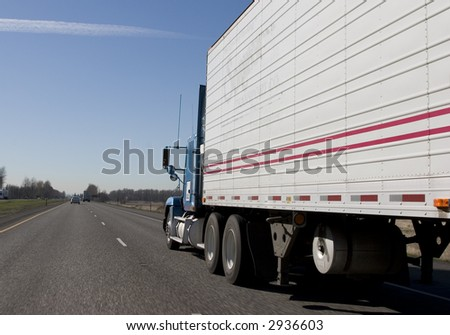 Big rig truck hauling freight down the highway - stock photo