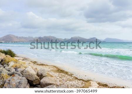 Big rocks on a seashore. Wavy sea near rocky beach. Transparent sea water. Storm on sea. Daylight sea. Sea water. Stormy sea day. Stormy clouds above the sea. Sea waves at storm. Storm waves, Majorca. - stock photo